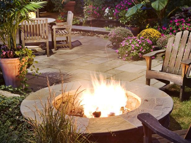 Fire Pit Surrounded by Chairs and Flowering Plants