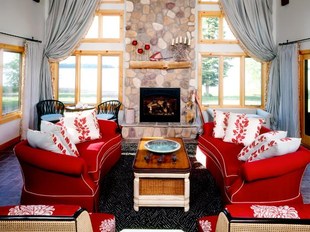 A pair of cherry red sofas brighten up this country living room. Floor-to-ceiling windows frame in the rustic stone fireplace and offer beautiful water views.