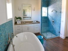 Glass tile in a stunning sea blue serves as the inspiration for this spa-like space, complete with vintage-style soaking tub and glass-enclosed shower.