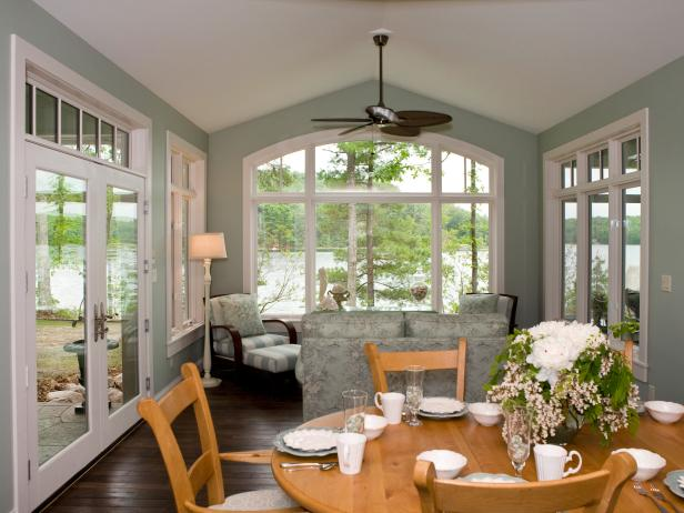 Spacious Cottage Sunroom With Ceiling Fan and Dining Area
