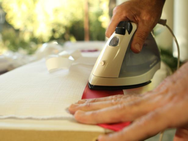 Ironing Red Ribbon on White Fabric