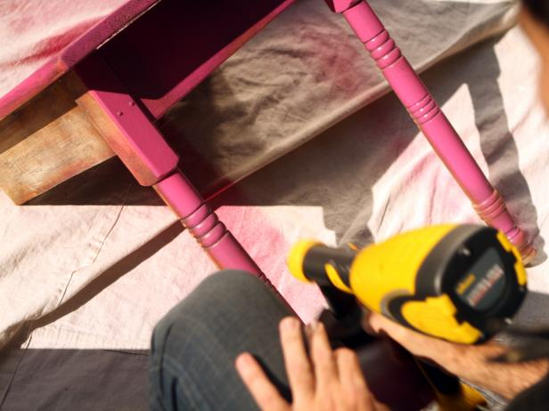 Apply an even base coat to table, keeping about eight inches' distance between table and sprayer to avoid paint buildup and dripping. Allow at least one hour for base coat to dry then apply a final coat.
