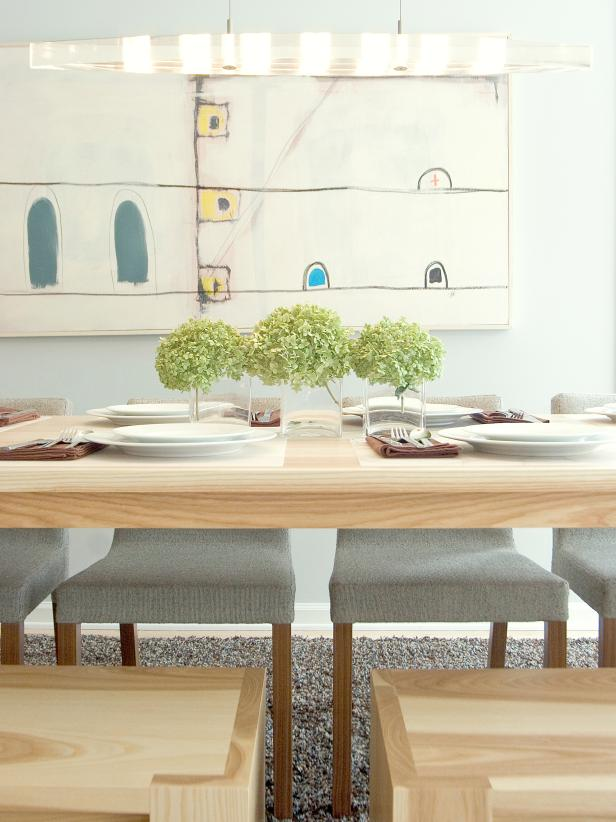 Natural Wood Dining Table Accented By Art and Gray Chairs