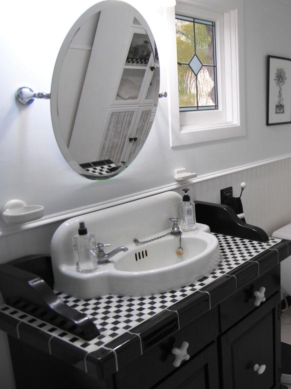 Black vanity with black and white tile in a small check pattern.