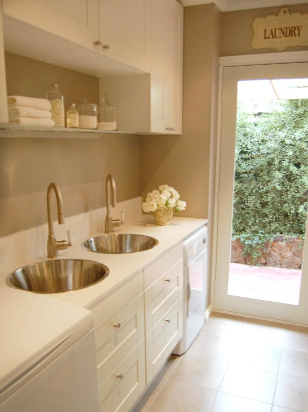 Beige Laundry Room With Two Sinks and White Cabinets
