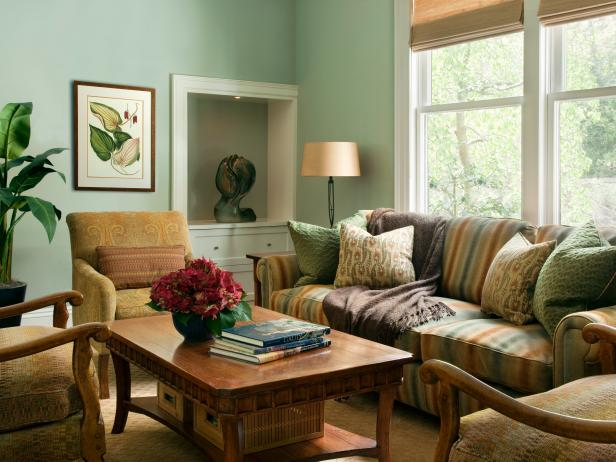Green living room with traditional furnishings in neutral tones.