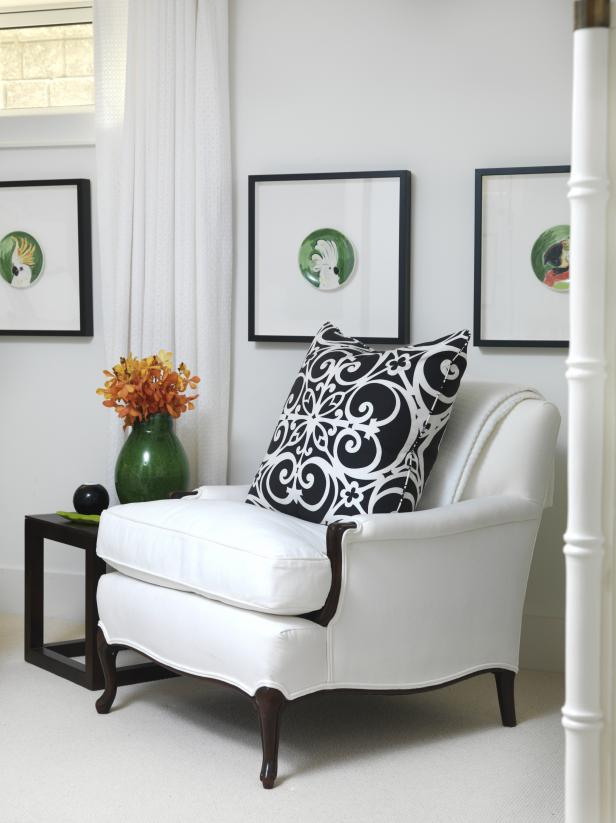 White Armchair With Black & White Pillow Beside Black End Table