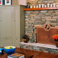 Country Living Room With Stone Trimmed Fireplace and Copper Screen