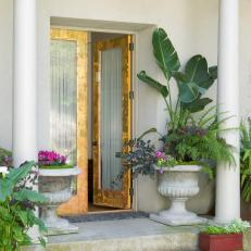 Mediterranean Style Entry With Greek Columns and Gold Doorway