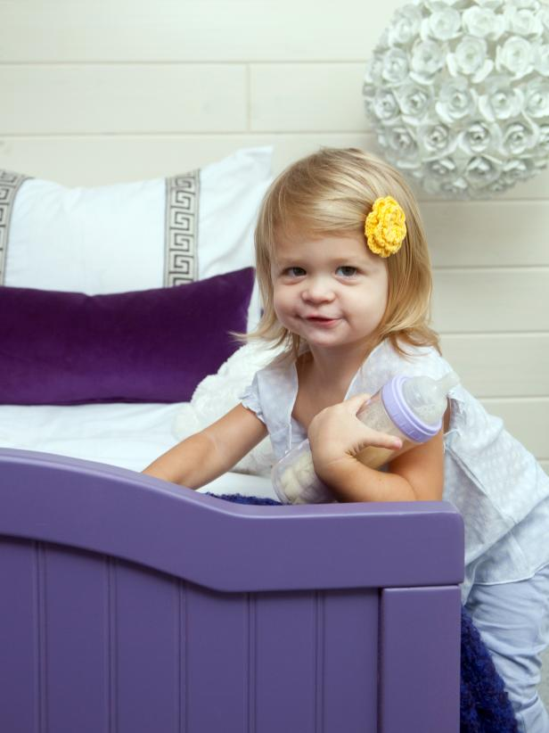 Girl Leaning Against Purple Bed