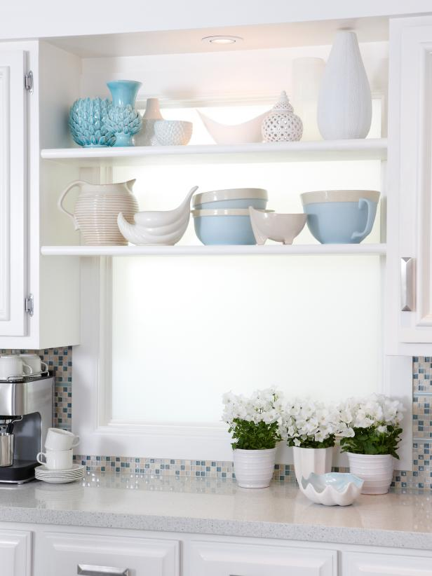 White Kitchen Window Shelf Displaying White and Blue Dishes and Vases