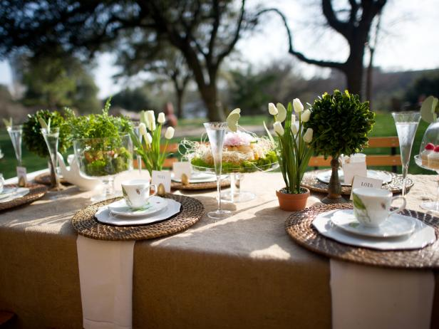 An outdoor tea party table setting, with white dishes and floral centerpieces.