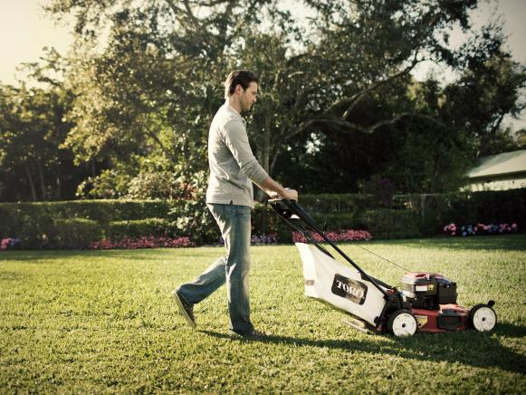 Man Mows Lawn on Summer Day