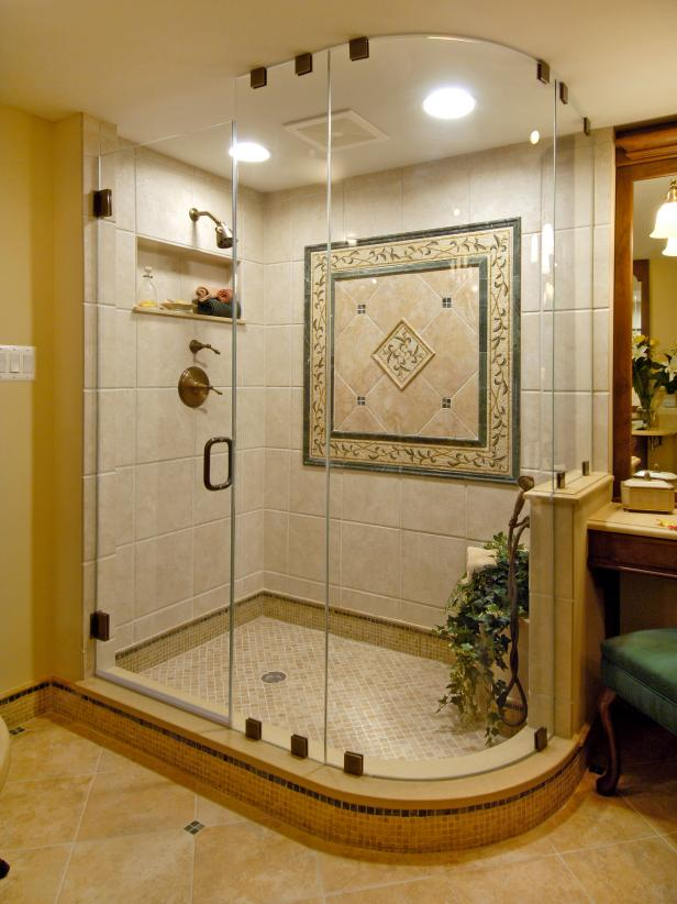 Shower With Curved Glass Enclosure, Faux Limestone and Tiled Medallion