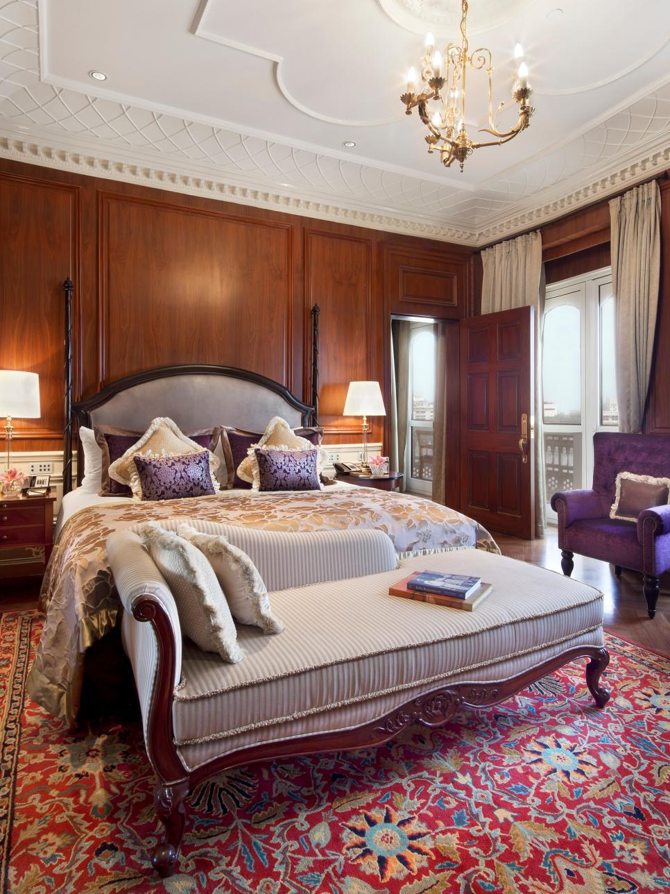 Traditional Wood Paneling Bedroom With Purple Armchair and Chandelier