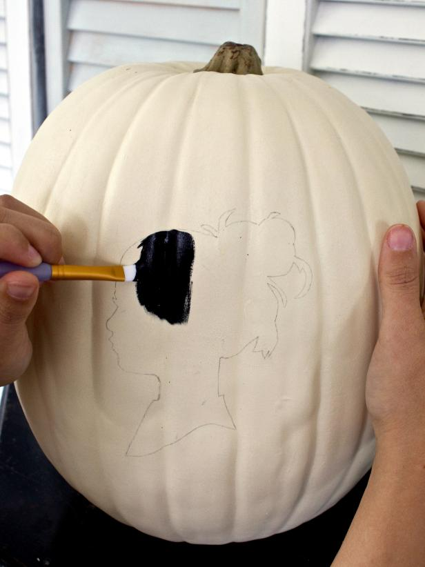 Remove the paper silhouette and stick pins, then use a flat-edged paintbrush to fill in the outline with black acrylic paint.