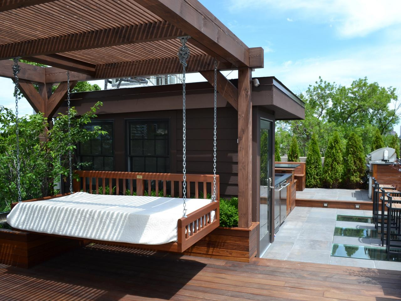 Urban outdoor patio with pergola and swinging daybed hgtv for Pergolas para patios