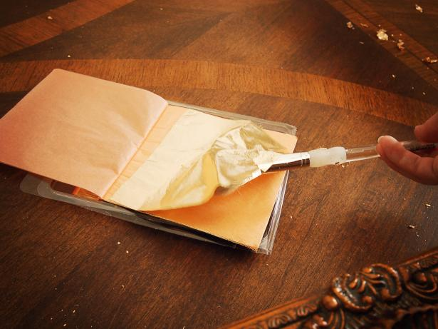 Use a soft brush to gently lift gold leaf sheet and apply to frame.