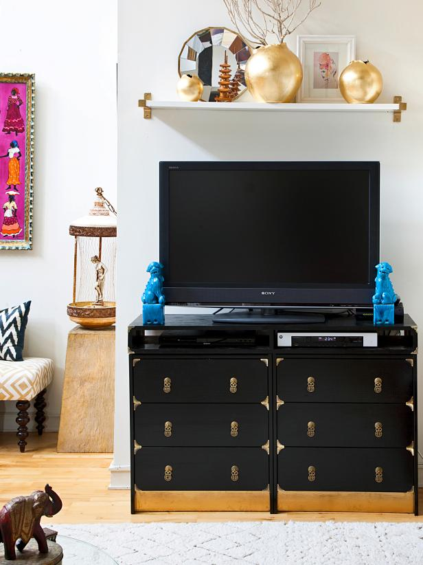 A black console is just as much the focal point as the television in this eclectic living room. A sprinkling of bohemian collectibles and printed textiles complete the living space.