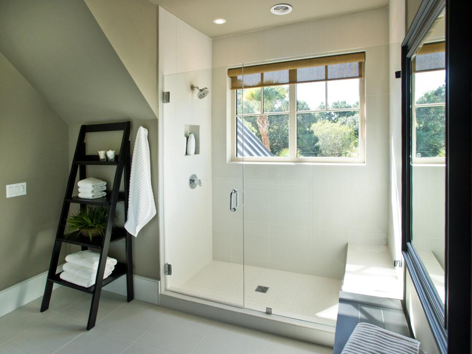 Bathroom With Glass Shower Doors and Black Easel-Style Shelf