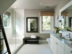 Crisp white porcelain tile and dark walnut-stained furnishings define this spa-like bathroom space.
