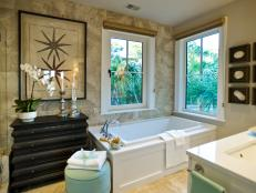 Travertine-style porcelain tile and white surfaces define this spa-like bath, where an antique-style dresser and botanical artwork offer an intriguing focal point.