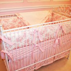 Pink Girl's Nursery With White Metal Crib and Toile Linens