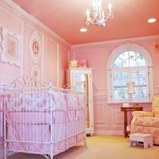 Pink Nursery With White Crib and Toile Fabric
