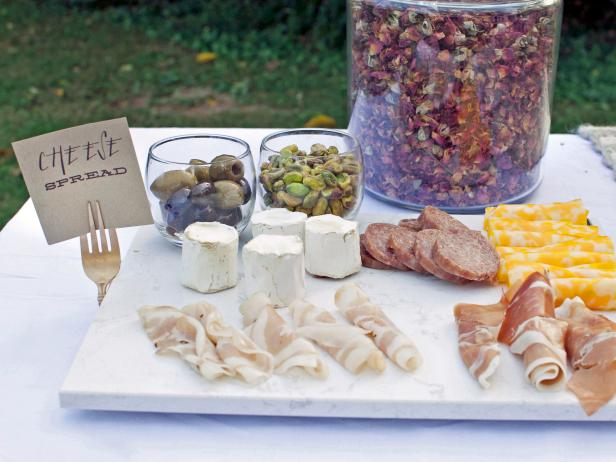 "A cheese plate makes ideal picnic food: It doesn't require cooking and it's bound to please a crowd. Present a mix of your favorite meats, cheeses and olives atop a marble board. Create your own food-tag holders by spray-painting discount metal forks and folding them into a ""U"" shape."
