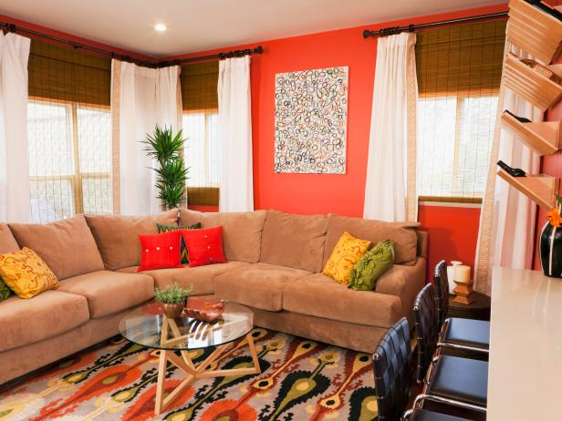 Living Room With Bamboo Shades, White Drapes and a Brown Sectional Sofa With Fiery Orange Walls