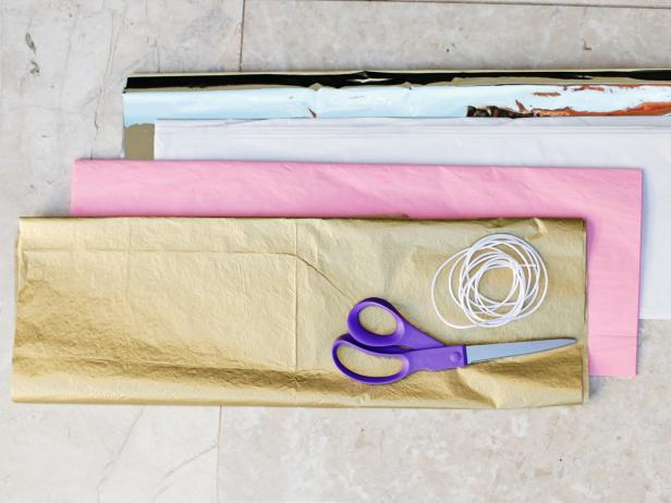 To start your tissue paper tassels, fold a piece of tissue paper in half and in half the other way.