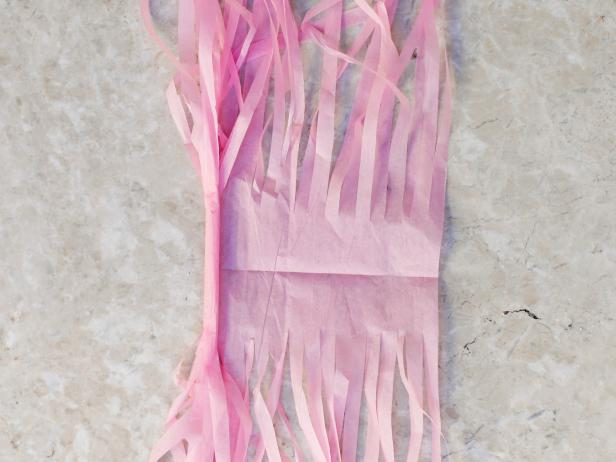 To create the tassels for the hanging garland, unfold tissue paper. Begin rolling tightly down the middle crease. Continue rolling, fold in half and then twist to create a loop for hanging.