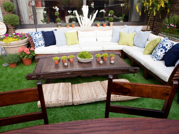 White Outdoor Sectional With Blue and Green Pillows & Brown Table