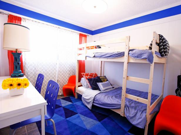 White Boys' Bedroom With Blue Geometric Rug, Red Curtains and Bunk Beds