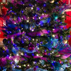christmas tree decorated in deep purple and peacock blue creates drama
