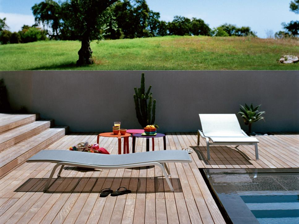 Contemporary Wood Pool Deck With Gray Chairs and Retaining Wall