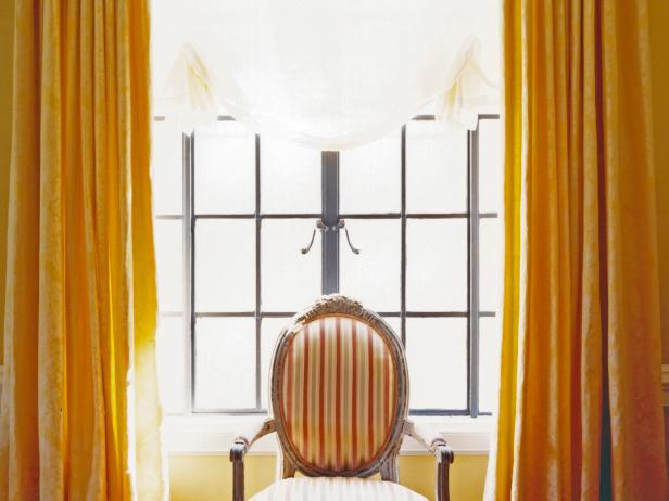 Gold Flowing Drapes in Front of a Large Pane of Old -Style Windows