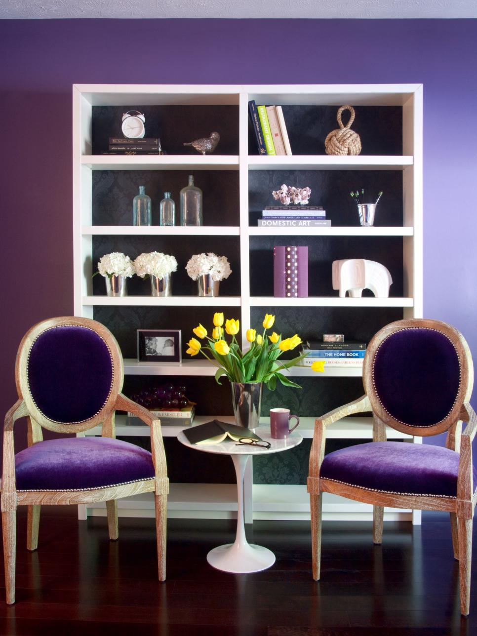 Purple room with white bookcase, velvet chairs and accessories.