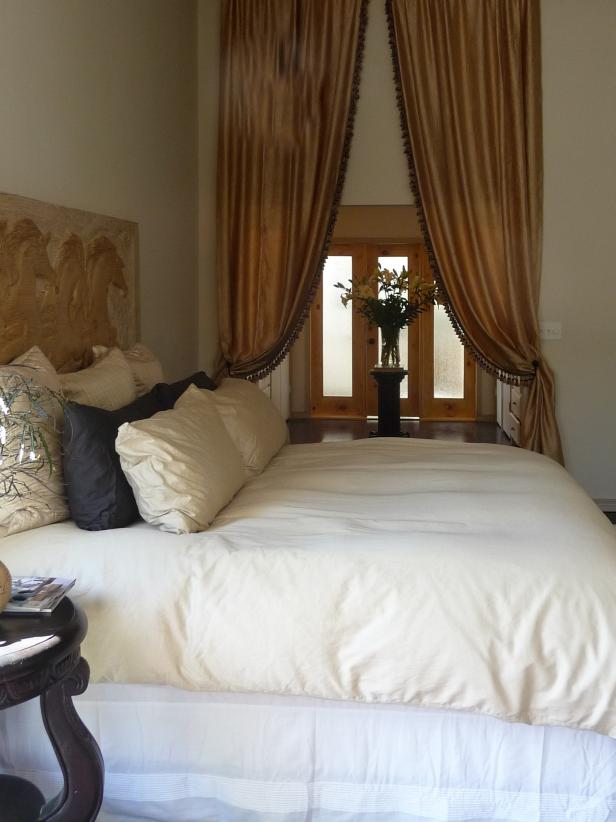 Transitional Bedroom With Plush White Bed and Gold Drapes