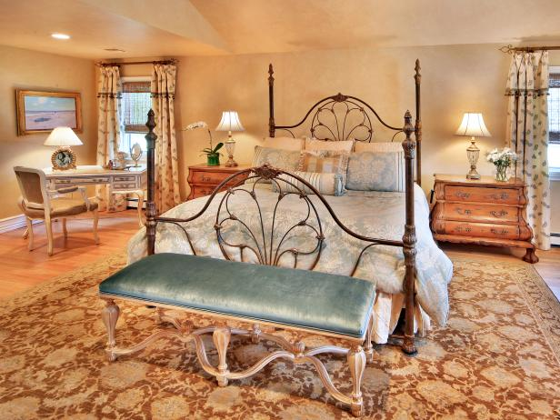 French Country bedroom with floral carpet, velvet bench and large iron bed frame.