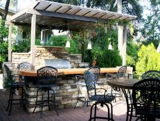 Outdoor Kitchen With a Bar Top and Eating Area