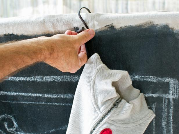 Place S-hooks or stocking hooks over the drapery rod, then hang up stockings on the finished faux chalkboard mantel.