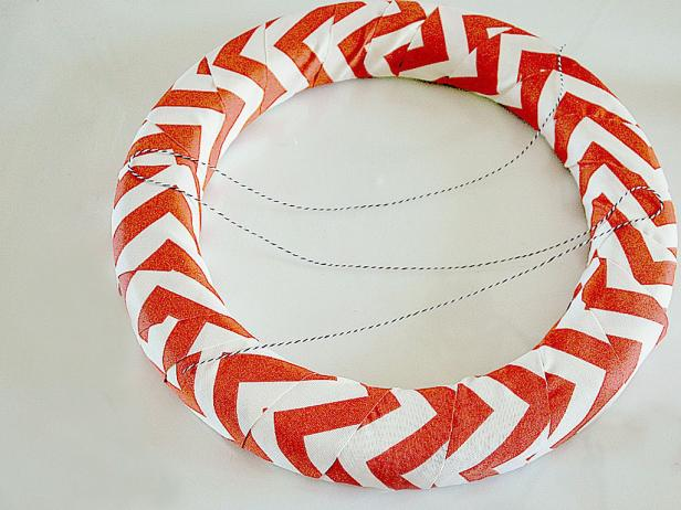 To start, wrap the orange fabric over the wreath form, slightly overlapping on the edges. Use your hot glue gun to attach the baker's twine onto the wreath, crisscrossing three times.