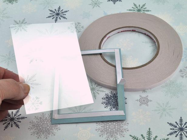 Cut window/acetate sheet slightly smaller than outside dimensions of frame. Line frame with high-tack, double-sided tape and peel release liner from tape for snow shaker holiday card.