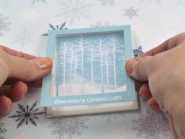 Carefully place window frame on top of the shaker base and burnish edges for snow shaker holiday card.