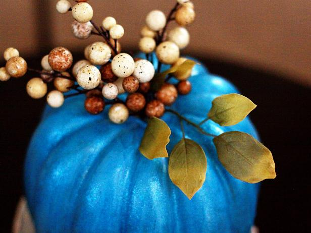 "Cut apart decorative ""holiday picks"" and glue them to the top of the pumpkins."
