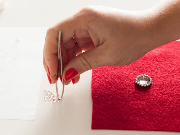 Pick up crystals with tweezers then apply glue to the backs before attaching it to the felt.