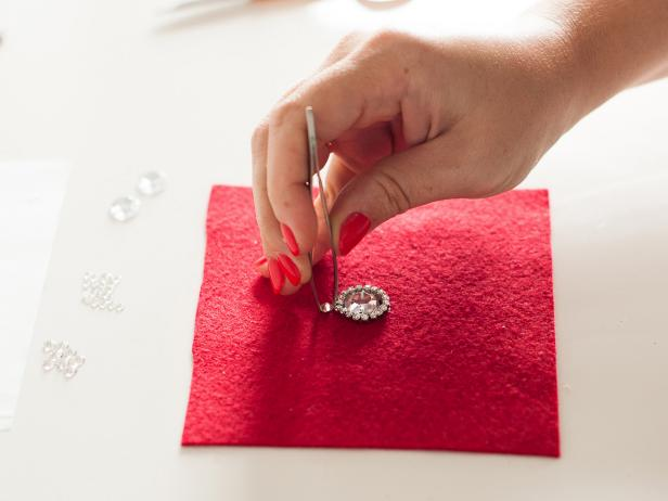Start applying the medium crystals around your design to create another circle. Tip: Pick up a crystal with tweezers then apply glue to the back before attaching it to the felt