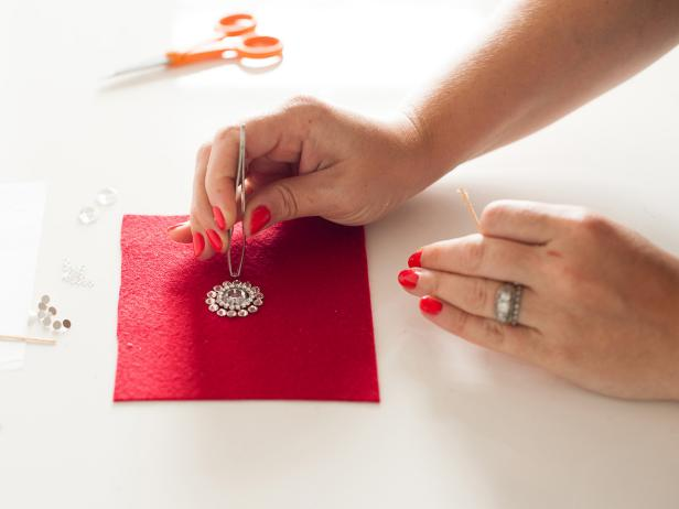 Start applying the medium crystals around your design to create another circle. Tip: Pick up a crystal with tweezers then apply glue to the back before attaching it to the felt.