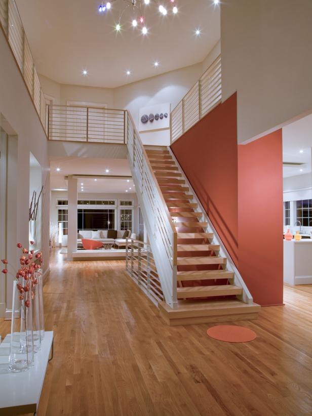 Neutral Foyer With Floating Stairs and Red Accent Wall